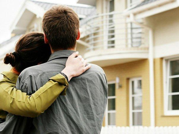 Парень с девушкой обнимаются возле дома