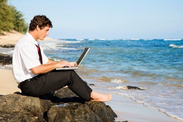Человек с ноутбуком возле моря