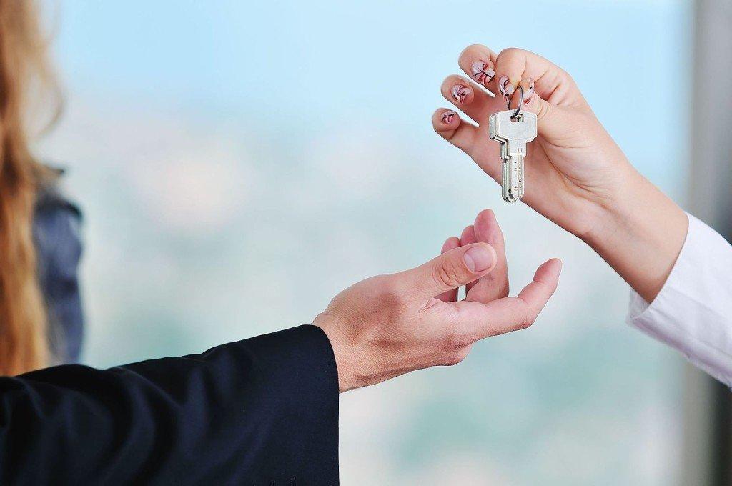 Женщина передает ключи от квартиры