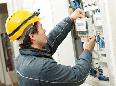 мужчина устанавливает электросчетчик в квартире