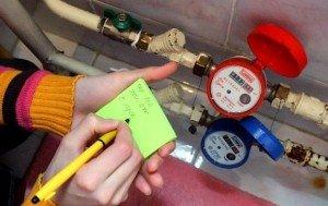 девушка записывает данные с счетчика воды